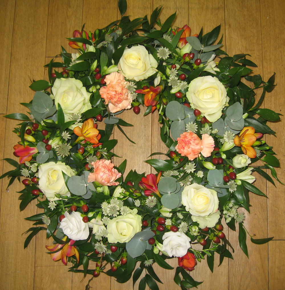 Red berry and white rose funeral wreath